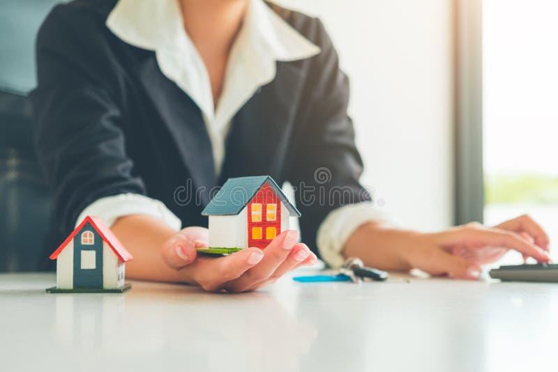 Kobieta agenta nieruchomości chwyt małego domu model w jej ręce, Ponownej obrazy stock