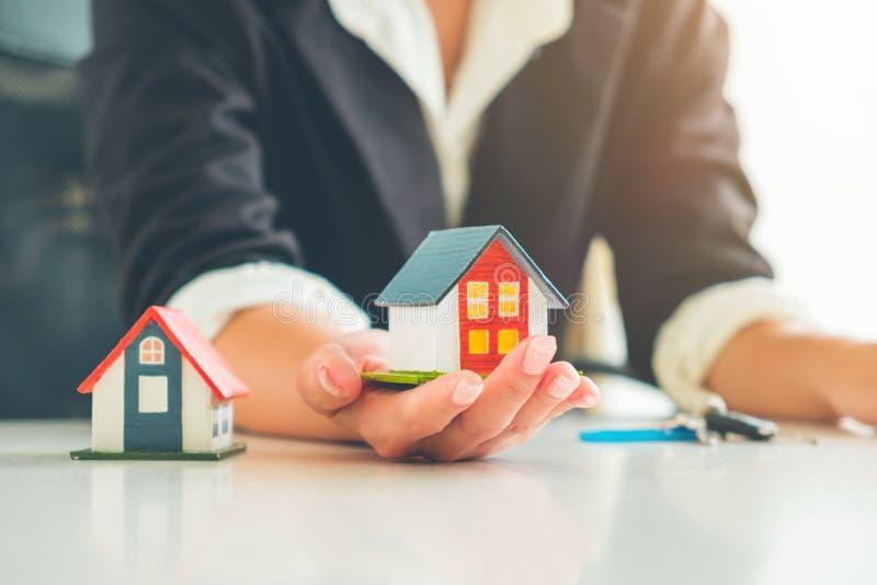 Kobieta agenta nieruchomości chwyt małego domu model w jej ręce, Ponownej obraz royalty free