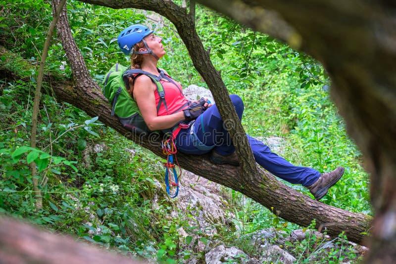 Kobieta alpinista odpoczywa na gałąź w Tureni-Copaceni wąwozie z błękitnym hełmem, Rumunia zdjęcia royalty free
