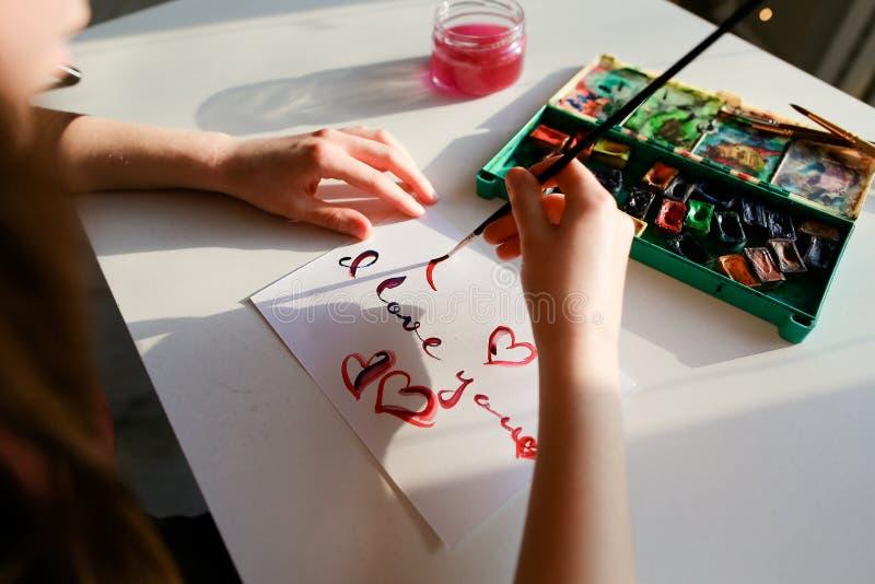Kobieta artysta w italikach pisze italik inskrypci na papierze s obrazy stock