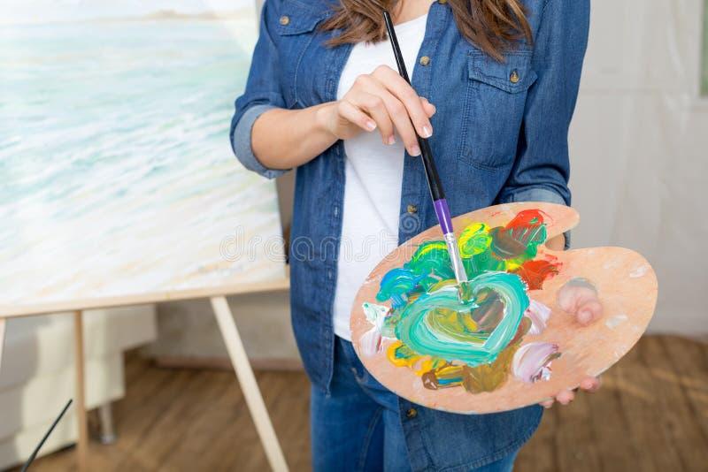 Kobieta artysty mienia paleta i paintbrush podczas gdy malujący obrazek obrazy stock
