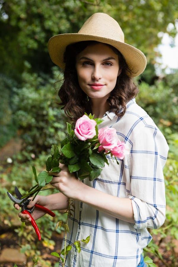 Kobieta arymaż kwitnie z przycinać strzyżenia w ogródzie na słonecznym dniu obraz stock