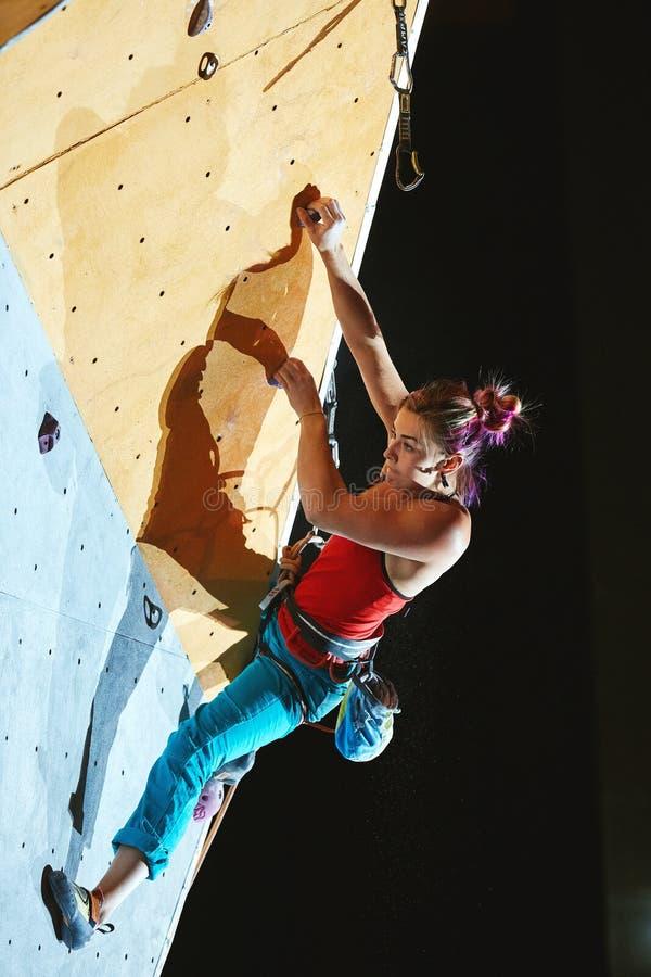 Kobieta arywista wspina się a z arkaną na wspinaczkowym gym obraz stock