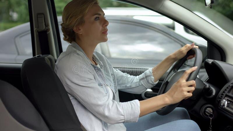 Kobieta attentively patrzeje drogę, ćwiczy jechać na koncesjonowanie kursie zdjęcia stock