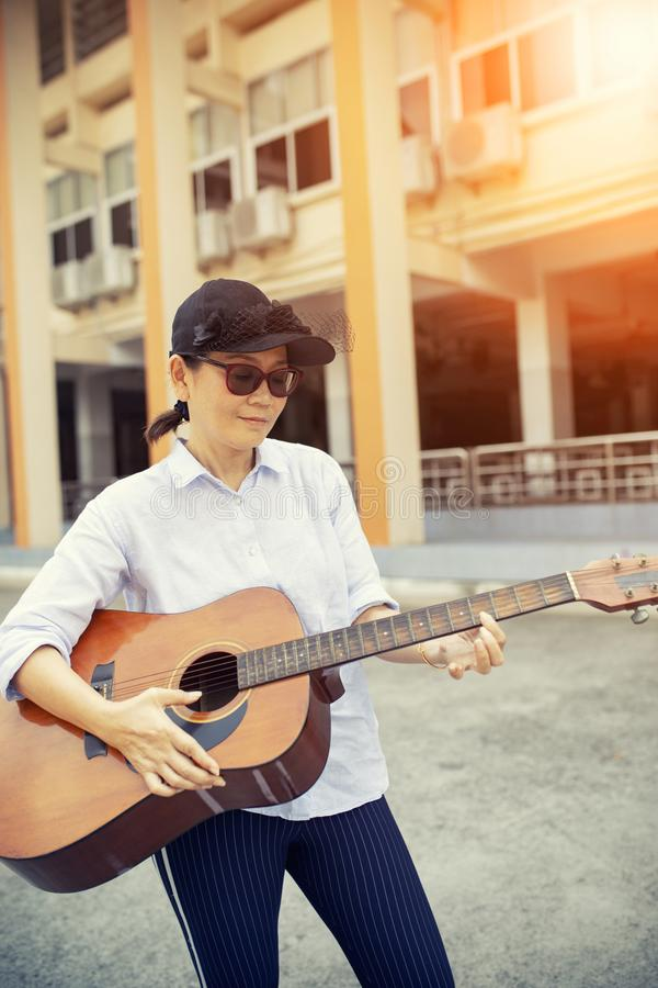 Kobieta bawić się gitarę akustyczną na ulicy stronie obraz stock