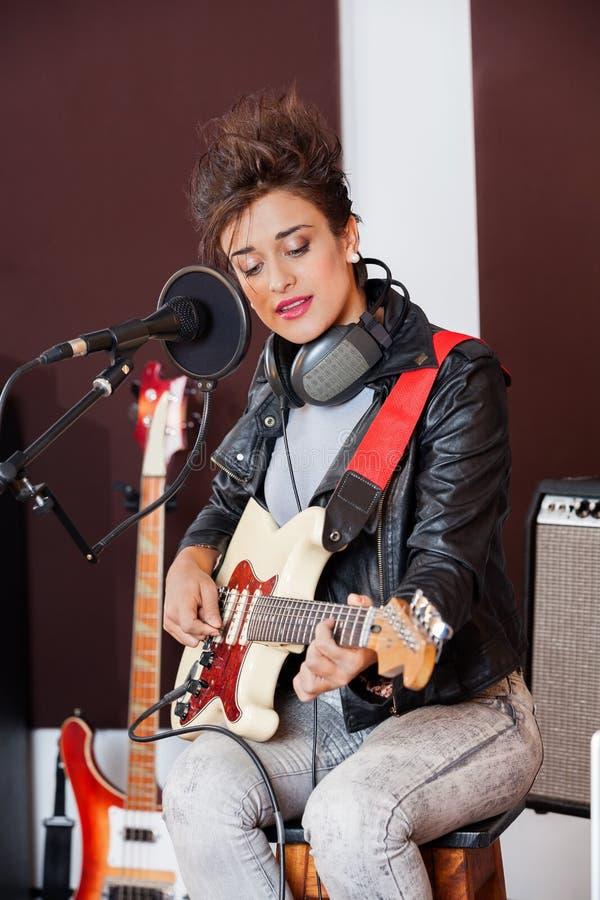 Kobieta bawić się gitarę w studiu nagrań fotografia stock