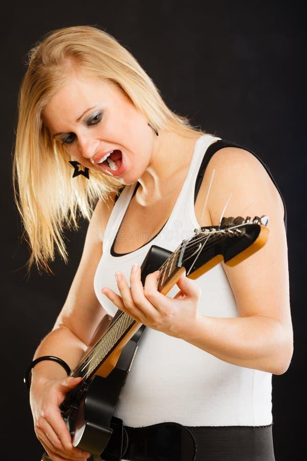 Kobieta bawić się na gitarze elektrycznej i śpiewie zdjęcie royalty free