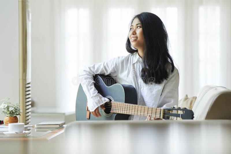 Kobieta bawić się na gitarze w domu obraz stock