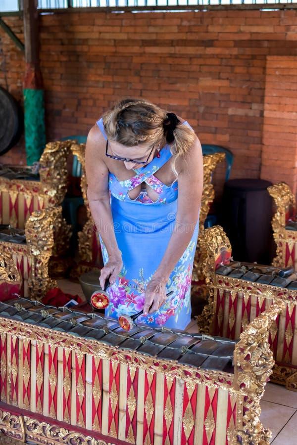 Kobieta bawić się na Tradycyjnego balijczyka muzycznym instrumencie gamelan bali piękny Indonesia wyspy kuta mężczyzna bieg kszta fotografia royalty free