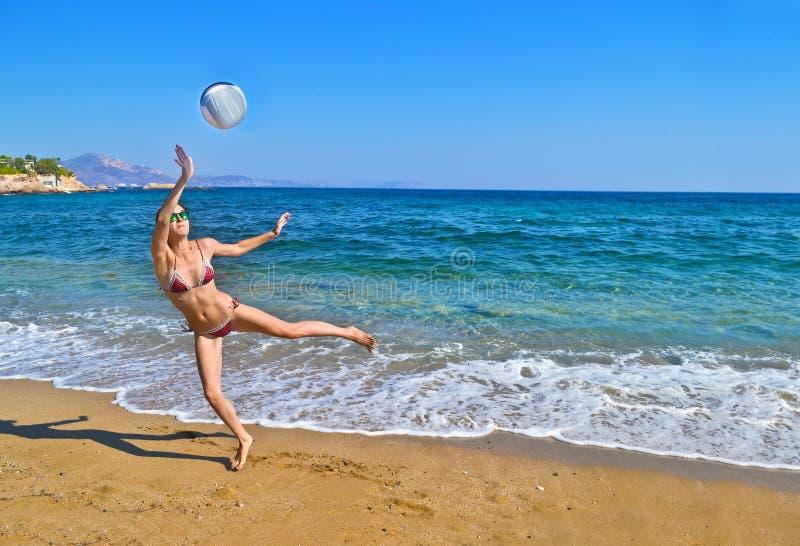 Kobieta bawić się siatkówkę przy grecką plażą zdjęcia royalty free