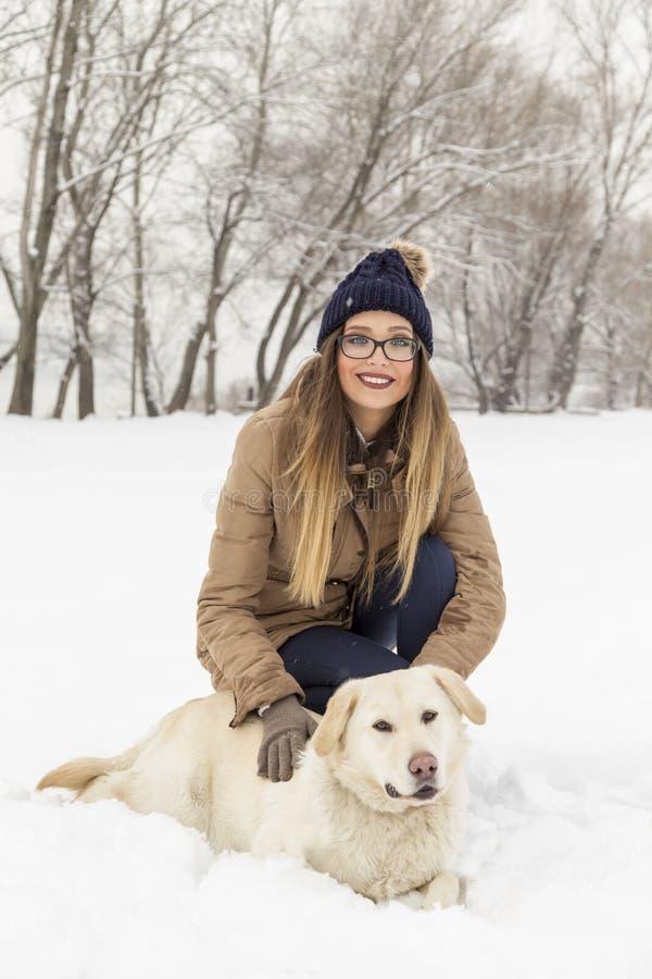 Kobieta bawić się z jej psem w śniegu fotografia stock
