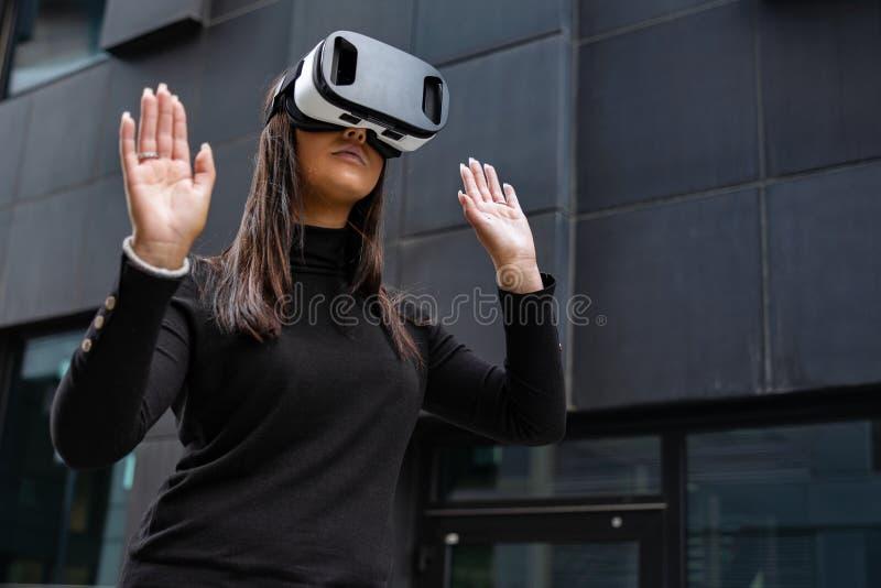 Kobieta Bawić się Z rzeczywistość wirtualna szkłami Przeciw Futurystycznej ścianie obraz stock