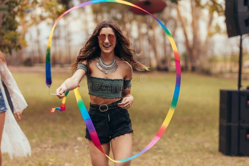 Kobieta bawić się z tasiemkowym kijem przy festiwalem muzyki fotografia stock
