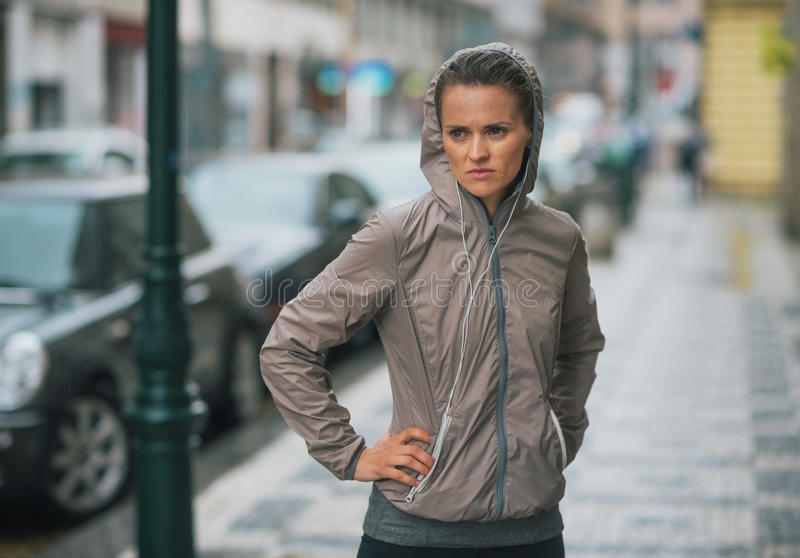 Kobieta biegacz jest ubranym podeszczową przekładnię zatrzymującą i czuć unmotivated fotografia royalty free
