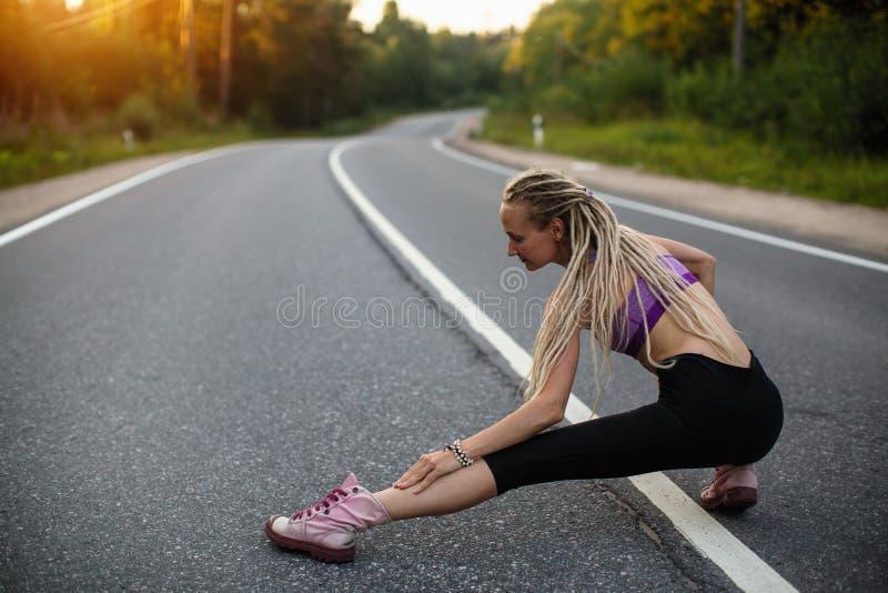 Kobieta biegacz rozgrzewkowy up na drodze przed Jogging sport obrazy royalty free