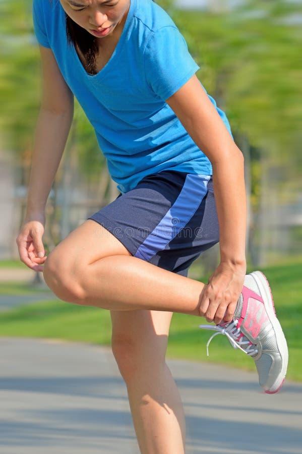 Kobieta biegacz trzyma ona sport raniąca kostka obraz royalty free