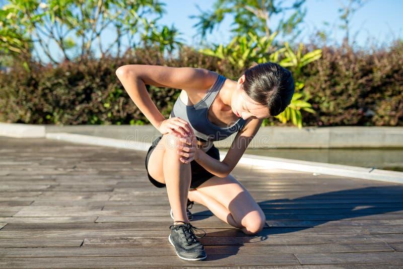Kobieta biegacz trzyma ona sport raniący kolano obrazy royalty free