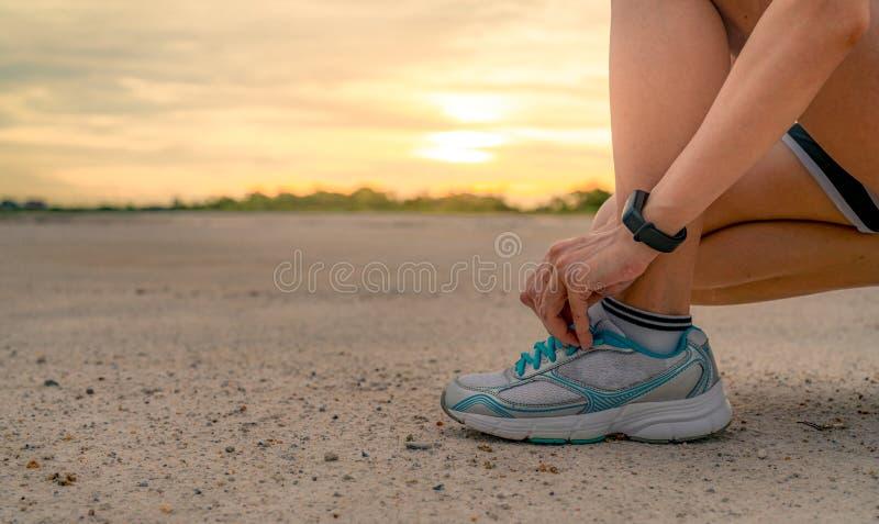 Kobieta biegacz wiąże sportów buty i dostaje gotowy dla bieg przy parkiem w ranku Azjatycki Żeński cardio ćwiczenie dla zdrowego  zdjęcie royalty free