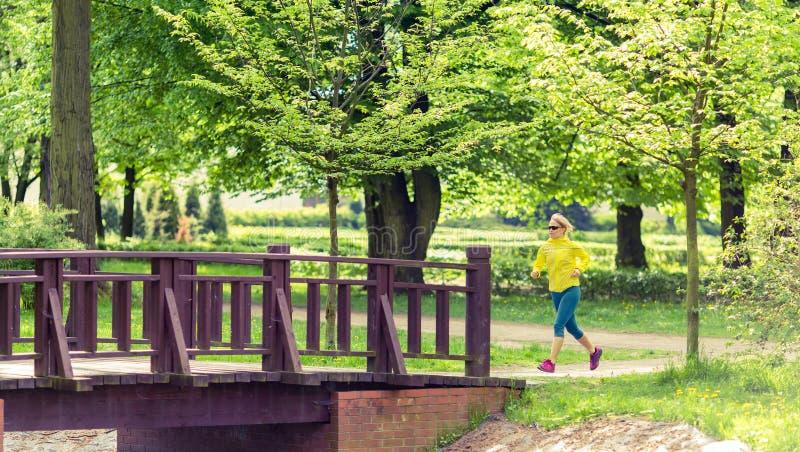 Kobieta biegacza bieg jogging w zielonym lato parku, drewnach i zdjęcie stock