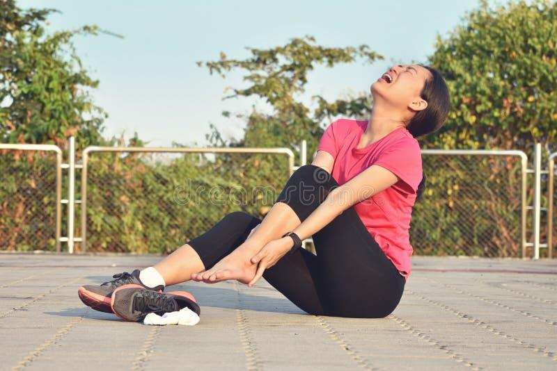 Kobieta biegacza kaleczenie trzyma bolesną zwichniętą kostkę w bólu obraz royalty free