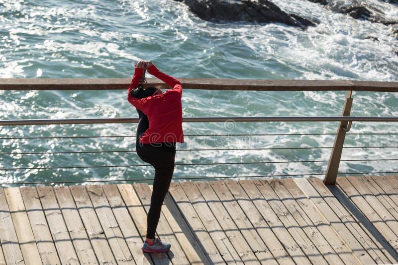 Kobieta biegacza rozciągania nogi na nadmorski boardwalk obrazy royalty free