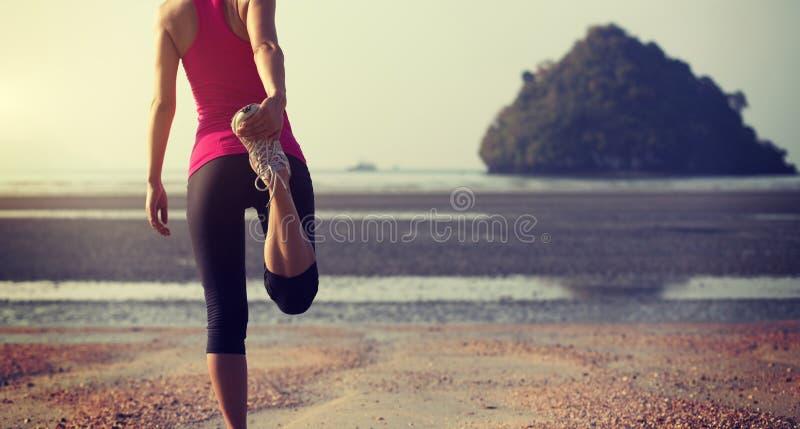 Kobieta biegacza rozciągania nogi przed biegać obraz royalty free