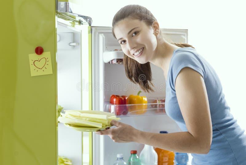 Kobieta bierze ?wie?ego seleru od fridge obraz royalty free