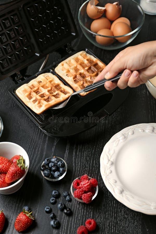Kobieta bierze świeżych opłatki z gofra żelaza w kuchni fotografia royalty free