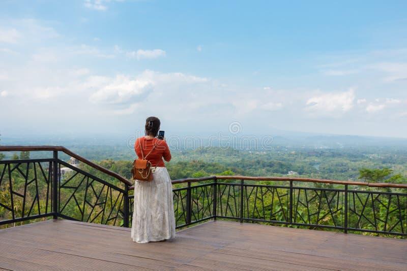 Kobieta bierze fotografię z jej telefonem sceniczna wieś od punktu obserwacyjnego zdjęcie stock