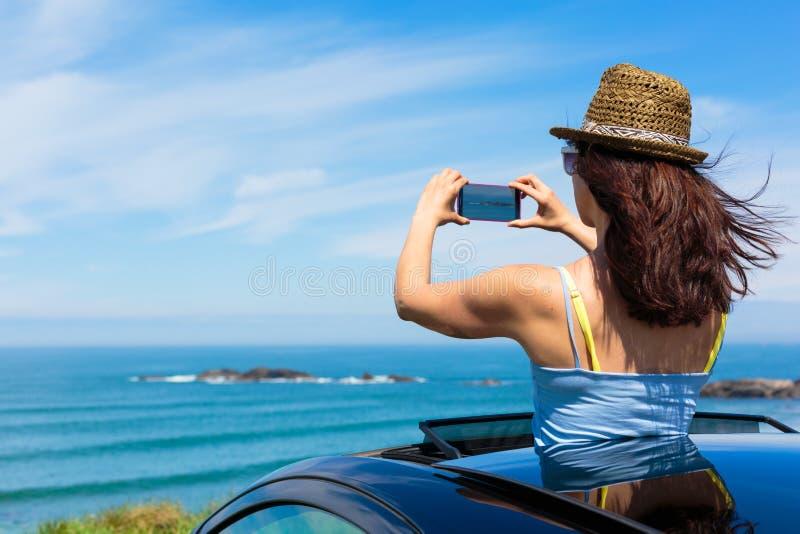 Kobieta bierze fotografię z smartphone kamerą na lato podróży zdjęcia royalty free