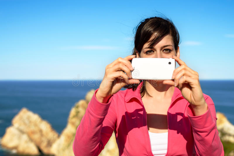 Kobieta bierze fotografię z telefonem komórkowym na lecie zdjęcie royalty free