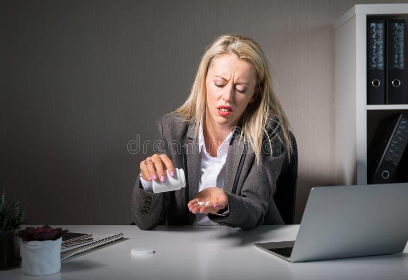 Kobieta bierze leki przy pracą zdjęcia stock
