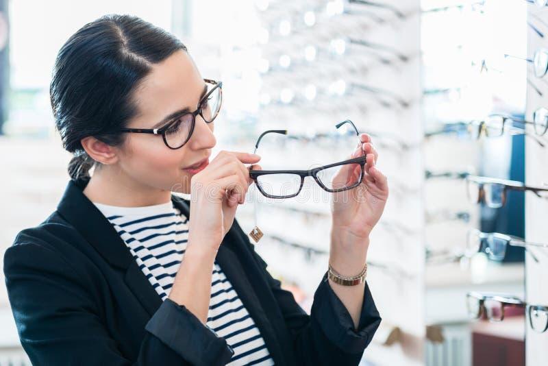 Kobieta bierze szkła z półki w okulisty sklepie obrazy stock