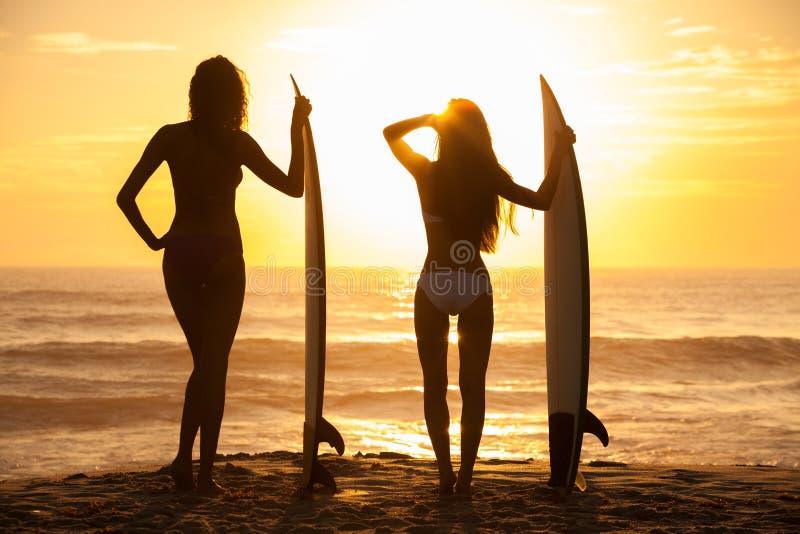 Kobieta bikini surfingowa Surfboards & dziewczyn zmierzchu plaża fotografia royalty free