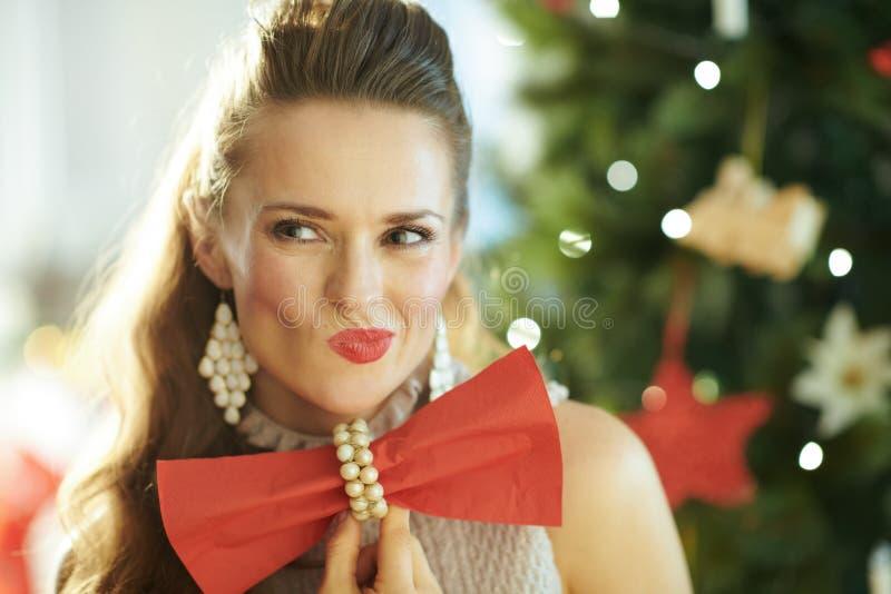 Kobieta blisko choinki mienia czerwonej obiadowej pieluchy jako łęku krawat obrazy royalty free