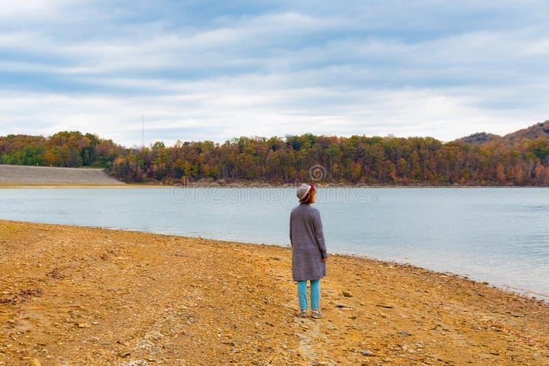 Kobieta blisko jeziora przy jesień sezonem cieszy się widok piękny dla obrazy stock