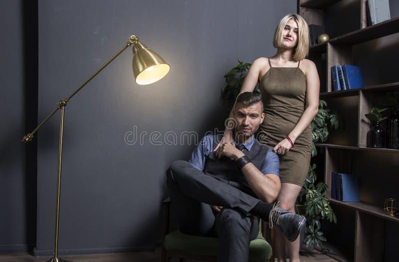 Kobieta blisko z pomyślnym bogatym człowiekiem Młody pomyślny biznesmen w krześle i jego seksownej kobiecie w sukni w luksusowym  zdjęcia stock