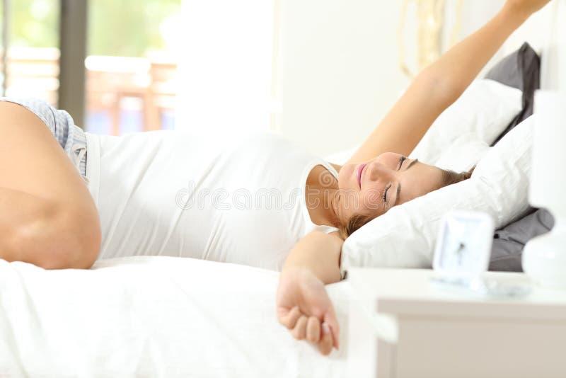 Kobieta budzi się rozciąganie ręki w ranku obraz stock