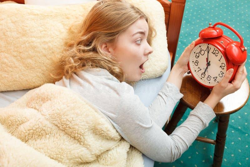 Kobieta budzi się up opóźnionego obracający daleko budzika obraz royalty free