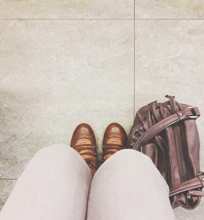 Kobieta buty obok torby na kafelkowej podłodze i nogi zdjęcie stock