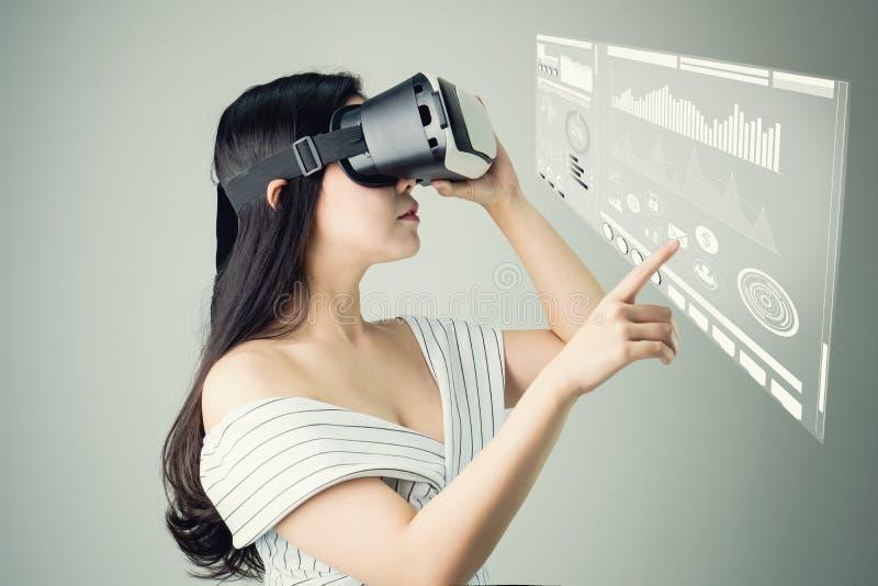 Kobieta był ubranym rzeczywistości wirtualnej słuchawki I dotyka ekranu technologii wykres która symuluje, obraz stock