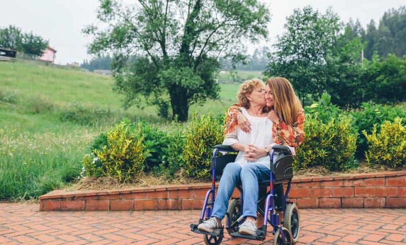 Kobieta całuje jej córki w wózku inwalidzkim obraz stock