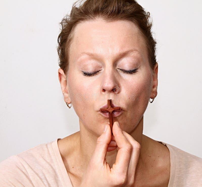Kobieta całuje krzyż w ona ręki fotografia stock