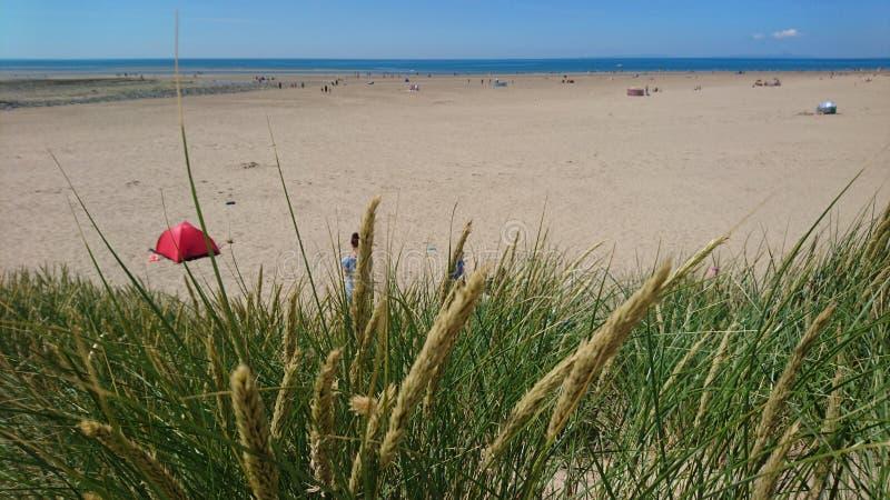 Kobieta, chłopiec i czerwień namiot na plaży, fotografia stock