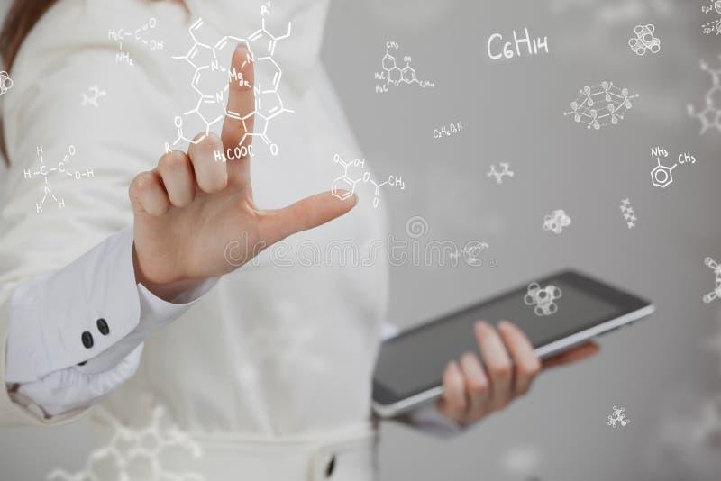 Kobieta chemik pracuje z chemicznymi formułami na popielatym tle zdjęcie stock