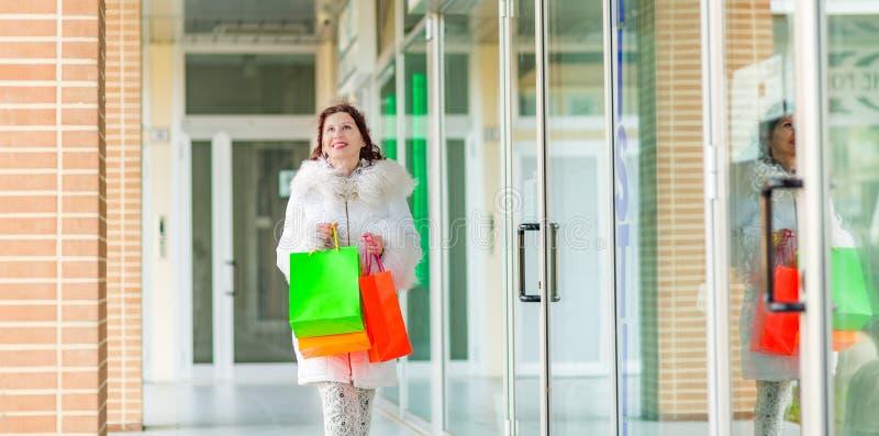Kobieta chodzi blisko sklepowych okno obraz royalty free