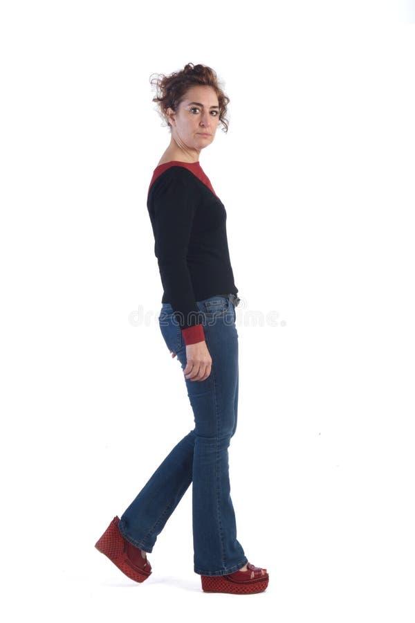 Kobieta chodzi na białym tle z niebieskimi dżinsami zdjęcia royalty free