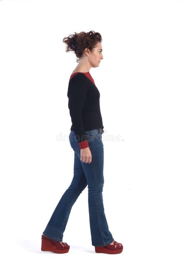 Kobieta chodzi na bielu z niebieskimi dżinsami zdjęcie stock