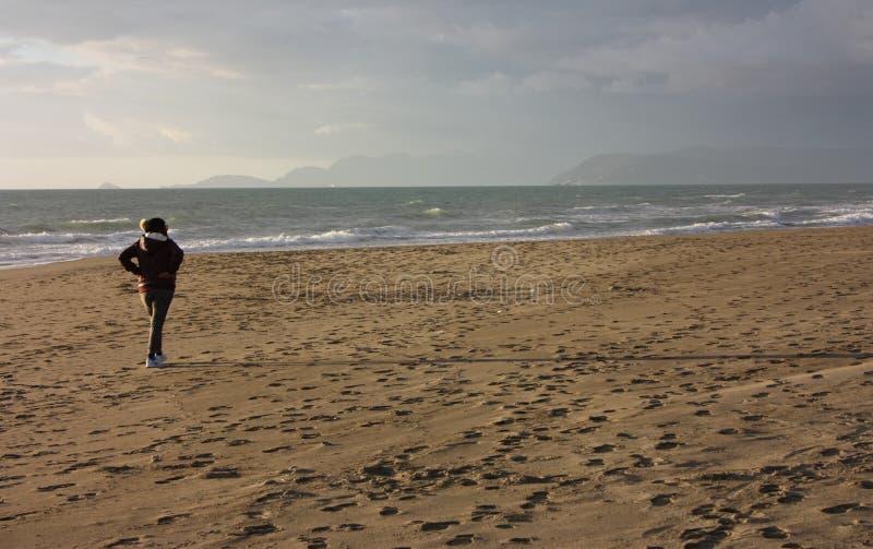 Kobieta chodzi spokojnego i zrelaksowanego na zima dniu chodzi na s bierze przerwę przy morzem, oddychać solankowym i opróżniać j obrazy royalty free