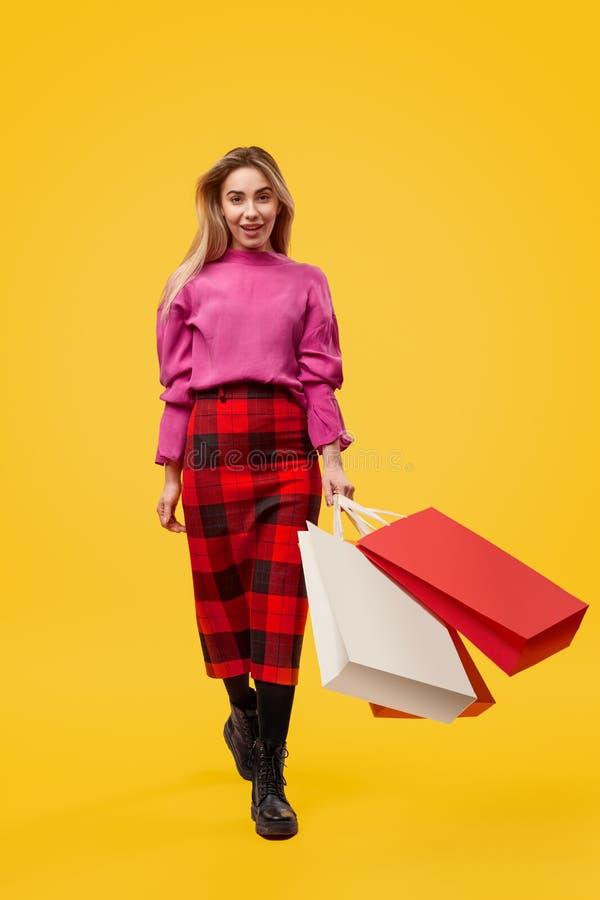 Kobieta chodzi w kierunku kamery z torbami na zakupy zdjęcia stock